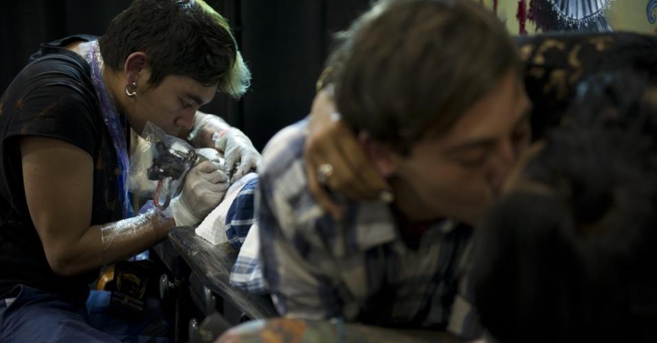 15.nov.2013 - Um tatuador desenha sobre o corpo de um cliente que beija a namorada na Bogota Tattoo Convention, em Bogotá, nesta sexta-feira (15). Cerca de 300 tatuadores de todo o mundo apresentam a sua arte na sétima edição do evento, que acontece entre 15 e 17 de novembro, e também conta com apresentações de dança e uma feira de roupas