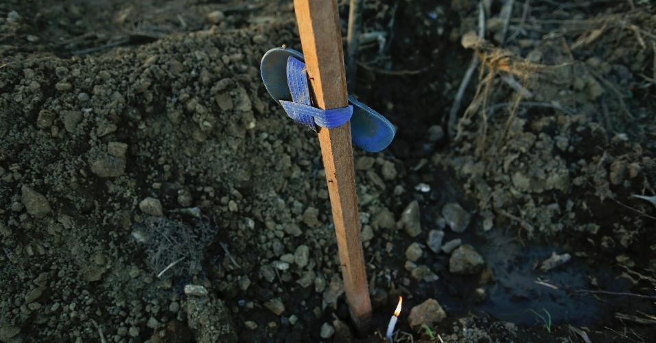 15.nov.2013 - Vela é acesa em uma vala comum onde cerca de 300 vítimas do tufão Haiyan foram enterradas em Palo, no sul de Tacloban, nas Filipinas