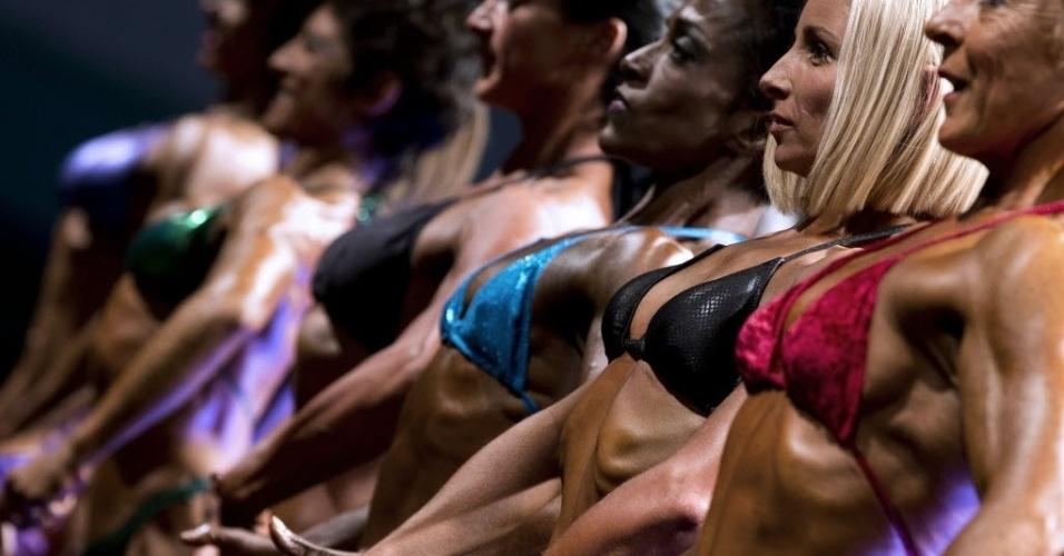 16.nov.2013 - Competidoras fazem fila em um campeonato de fisiculturismo neste sábado (16), em Paris. A competição mundial é promovida pela Natural Body Building International Union