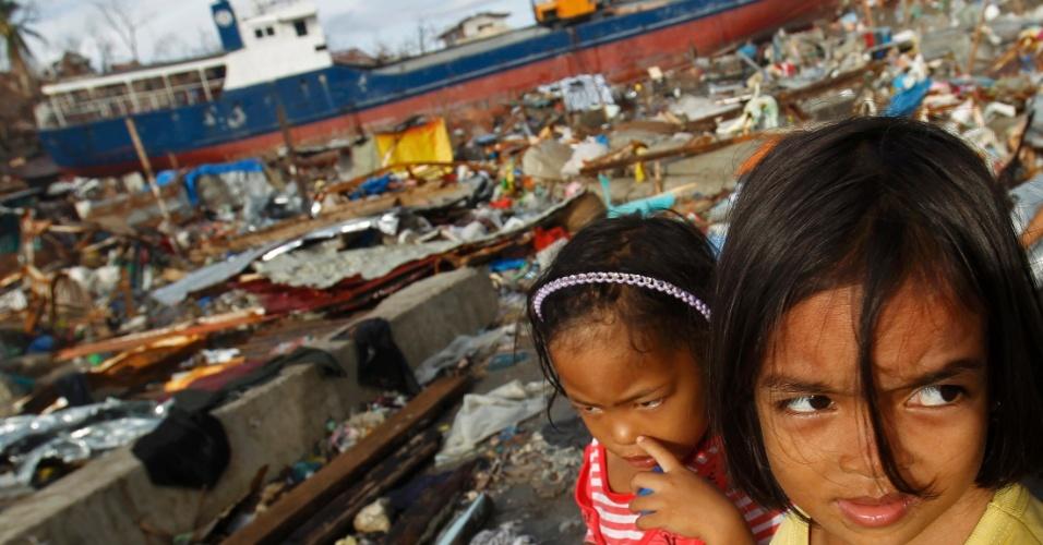 16.nov.2013 - Garotas observam região de Tacloban (Filipinas) destruída por passagem do tufão Haiyan. Ondas de até cinco metros levaram navios à terra