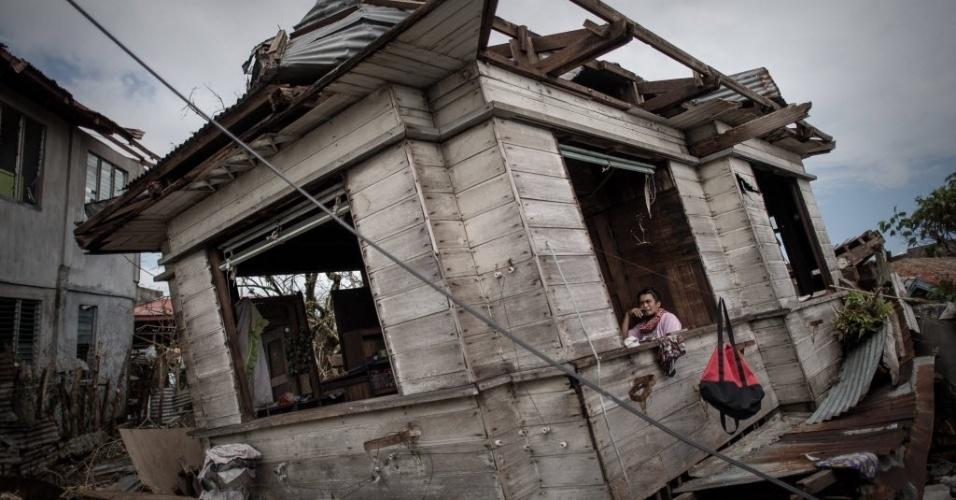 16.nov.2013 - Um sobrevivente do tufão Haiyan aparece na janela de sua casa em Tanauan, no leste da ilha de Leyte, neste sábado (16). Liderados por um grupo de porta-aviões dos EUA, os esforços de ajuda estrangeiras têm se intensificado nas Filipinas, oito dias depois que o super tufão Haiyan deixou milhares de mortos e milhões de desabrigados no país.