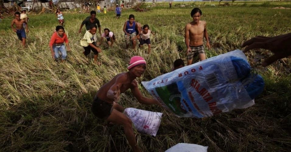 16.nov.2013- Moradores de uma vila afetada pelo tufão Haiyan, nas Filipinas, recebem mantimentos que são jogados de um helicóptero militar neste sábado (16). A vila de Aubyog é de difícil acesso, e fica em uma das regiões mais afetadas pelo tufão