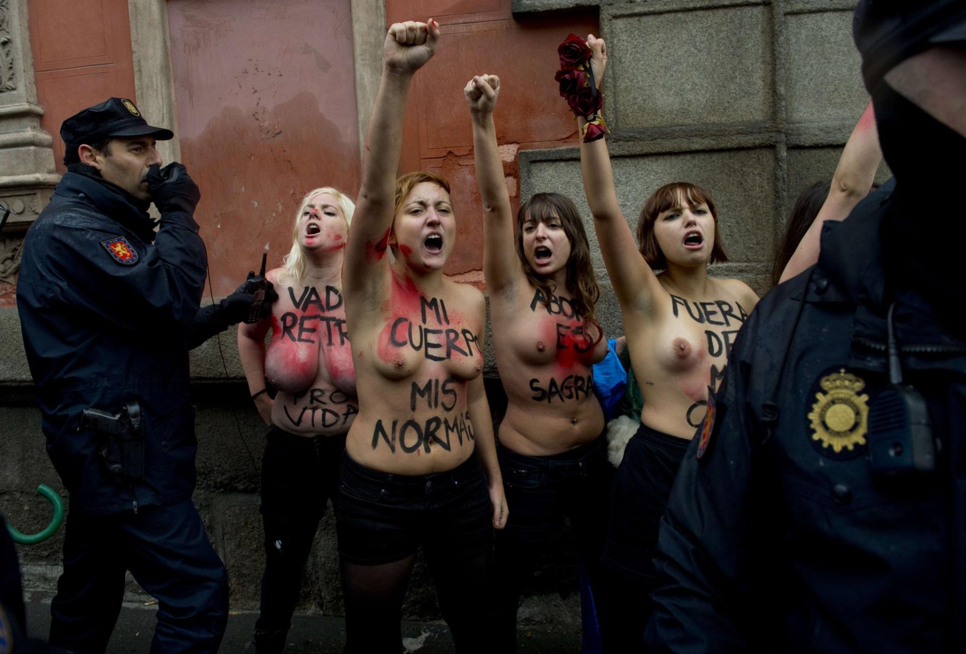 17.nov.2013 - Ativistas do Femen, famoso por protestos com mulheres seminuas, são rodeadas por policiais durante protesto contra uma marcha anti-aborto em Madri (Espanha), neste domingo (17)