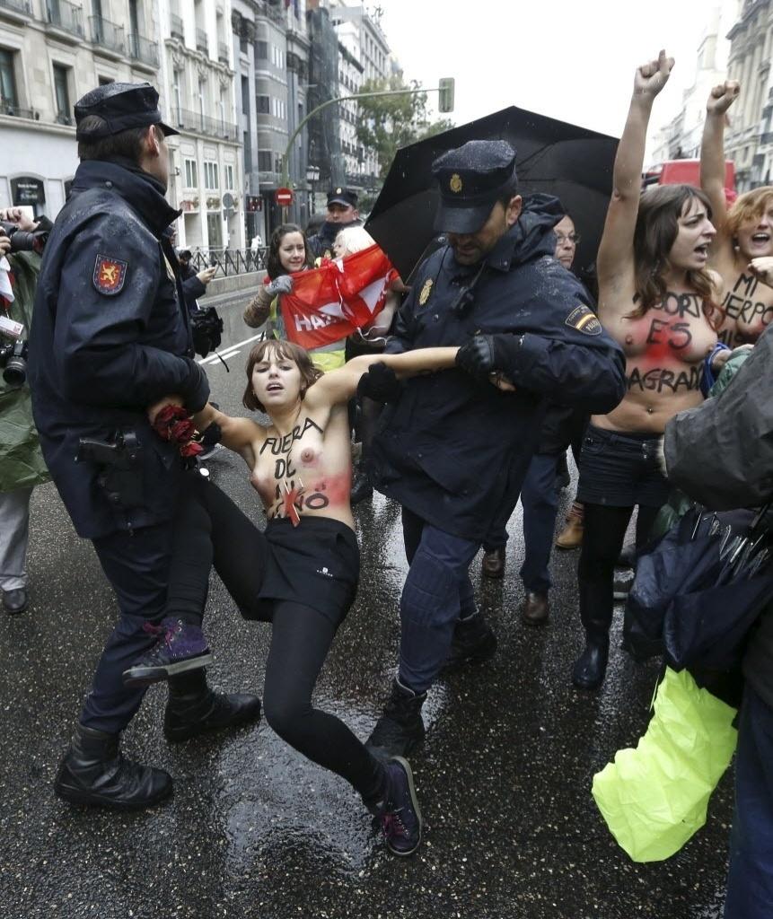 17.nov.2013 - Uma ativista do Femen, famoso por protestos com mulheres seminuas, é carregadas por policiais durante ato contra uma marcha anti-aborto em Madri (Espanha), neste domingo (17)