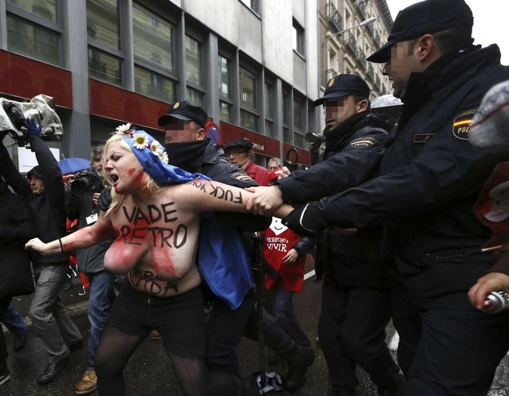 17.nov.2013 - Uma ativista do Femen, famoso por protestos com mulheres seminuas, é presa por policiais durante ato contra uma marcha anti-aborto em Madri (Espanha), neste domingo (17)