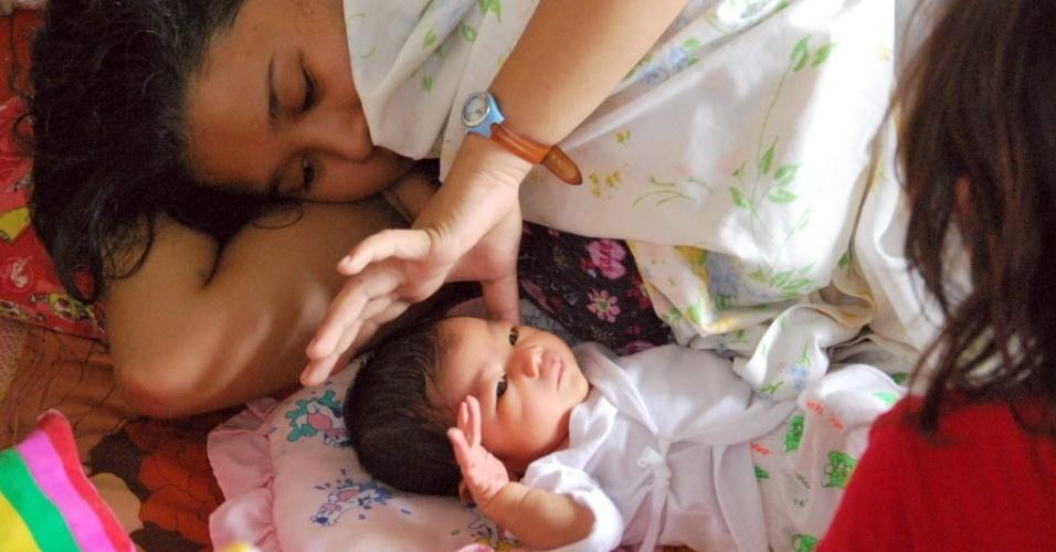 17.nov.2013 - Queen Angel, uma menina com dois dias de vida, é acariciada por sua mãe, Angelina Maron, 24, em Cebu, nas Filipinas. Prestes a dar à luz, Angelina passou dias com muito calor e pouca comida. Seu marido ficou protegendo a casa da família, em San Jose. O pai de Angelina está desaparecido.