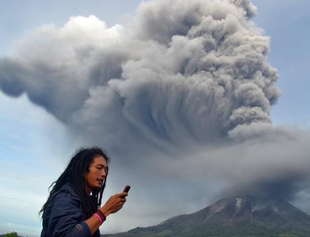 18.nov.2013 - Homem usa celular diante do Monte Sinabung, que voltou a entrar em erupção na ilha indonésia de Sumatra. A Indonésia está em alerta devido à erupção do Sinabung e do vulcão Merapi, em Java