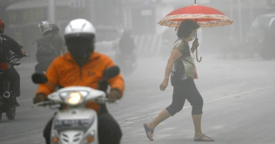 18.nov.2013 - Mulher atravessa rua de Boyolali, na ilha indonésia de Java, encoberta por fumaça expelida pelo vulcão Merapi. A Indonésia está em alerta devido à erupção dos vulcões Sinabung e Merapi
