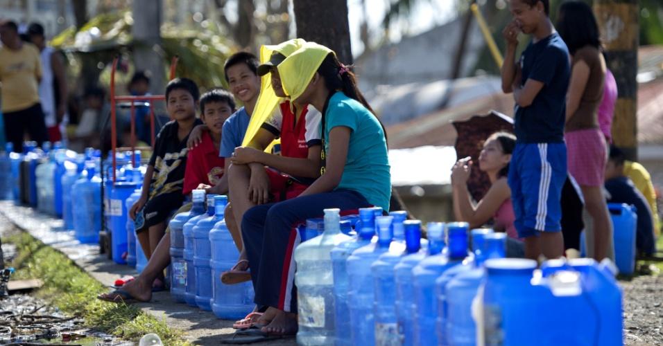 18.nov.2013 - Vítimas do tufão Haiyan fazem fila com galões em estação de purificação de água em Tacloban nesta segunda-feira (18). Diversas comunidades filipinas sofrem com problemas no abastecimento de água após a passagem pelo país da maior tempestade já registrada