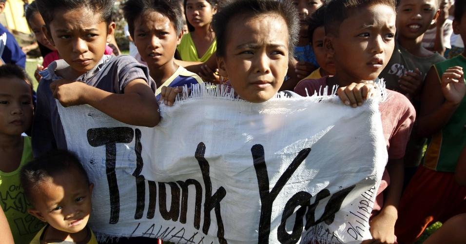 19.nov.2013 - Crianças filipinas seguram cartaz de agradecimento após um helicóptero da Marinha dos EUA deixar mantimentos na cidade de Lawaan, em Samar