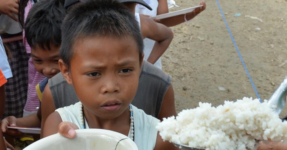 19.nov.2013 - Garoto recebe comida distribuída pelo governo das Filipinas em Hernani, uma das regiões afetadas pela passagem do tufão Haiyan no país