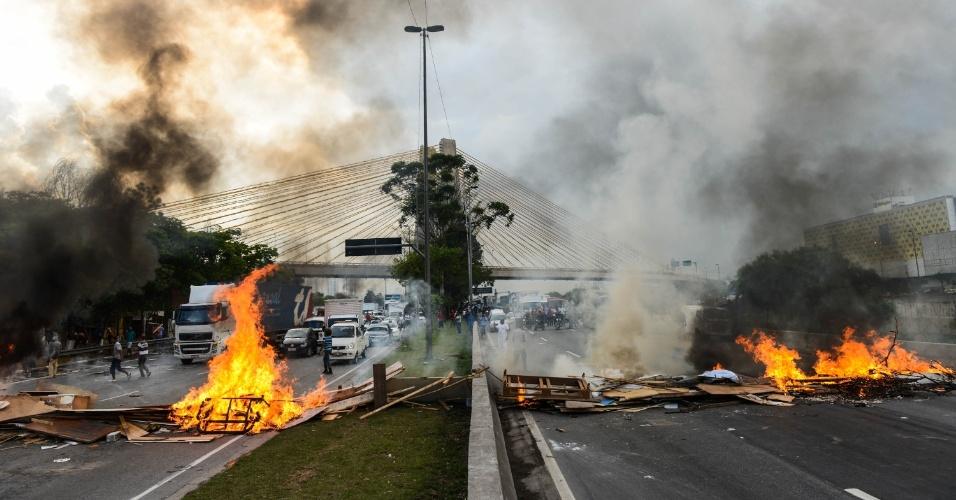 19.nov.2013 - Moradores da comunidade Estaiadinha interditaram a pista da marginal Tietê, em São Paulo, nesta terça-feira (19). Eles atearam fogo em madeira para impedir a passagem dos veículos. A comunidade foi alvo de reintegração de posse no sábado (16). O protesto foi encerrado no início da noite