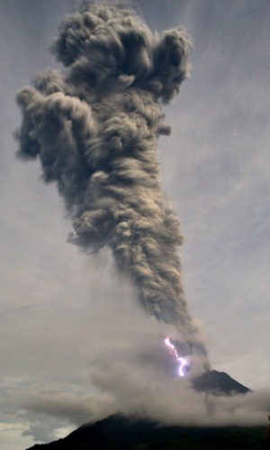 19.nov.2013 - Relâmpago ocorre ao vulcão Sinabung expelir cinzas e fumaça quente, no oeste da ilha de Sumatra (Indonésia). O Sinabung está em atividade desde meados de setembro, cuspindo de cinzas vulcânicas a uma altitude em torno de 10 mil metros. O raio é formado pela fricção das partículas quentes com alta energia