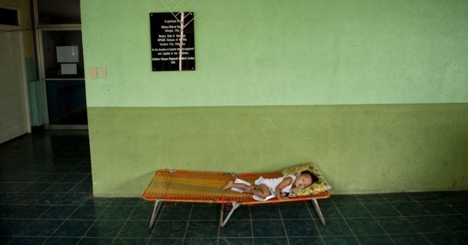 20.nov.2013 - Criança dorme em cama imrpovisada do lado de fora do superlotado hospital infantil em Tacloban, nas Filipinas, nesta quarta-feira (20). Crianças com diversos tipos de lesões e bebês recém-nascidos lotam o espaço limitado do hospital, gravemente danificado pelo tufão Haiyan