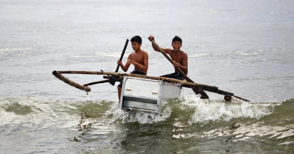 20.nov.2013 - Meninos se locomovem em barco feito com uma geladeira quebrada e pedaços de bambu em direção a praia em Tanauan, nas Filipinas, nesta quarta-feira (20). Após perderem suas casas e barcos com a passagem do tufão Haiyan, pescadores de vila destruída em Tanauan começaram a criar barcos com refrigeradores abandonados. O primeiro barco do tipo foi feito por um pescador a partir de ideia de crianças, que queriam brincar com a embarcação improvisada. A ideia foi seguida por outros pescadores e tornou-se uma alternativa para o transporte por água na região. Mais de 4.000 pessoas morreram e milhões ficaram desabrigadas