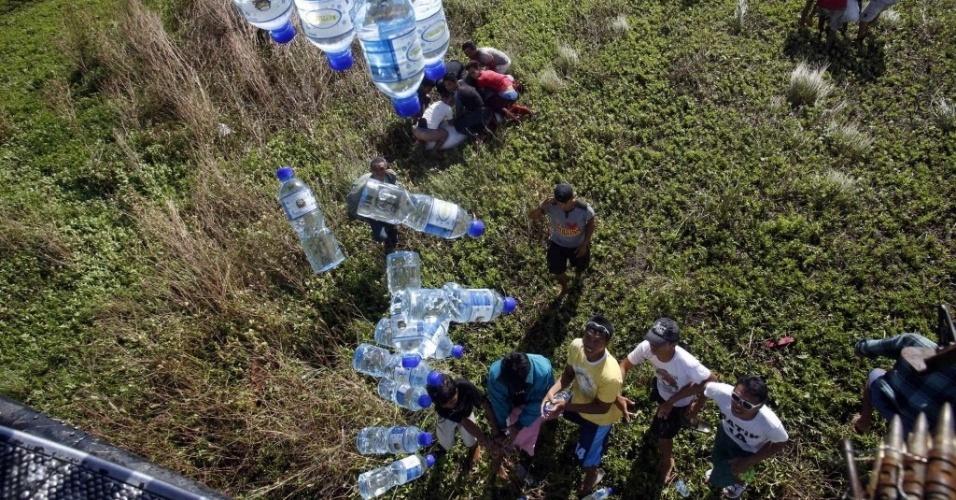 21.nov.2013 - Helicóptero militar filipino distribui água para s sobreviventes em Tolosa, região central das Filipinas.  A organização Médicos Sem Fronteiras insistiu nesta quinta-feira que a ajuda humanitária ainda não chegou a centenas de vítimas nas áreas mais remotas do país