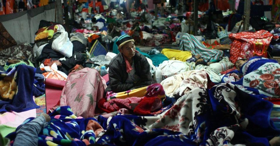 21.nov.2013 - Indonésios se acomodam em abrigo na vila Tiga Nderket, na ilha de Sumatra (Indonésia), por causa da erupção do vulcão Sinabung, em Karo