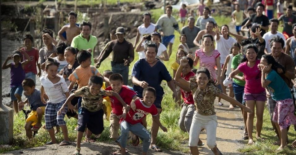 21.nov.2013 - Moradores correm para chegar a um helicóptero da Força Aérea com mantimentos para a aldeia de pescadores perto Caragari, nas Filipinas