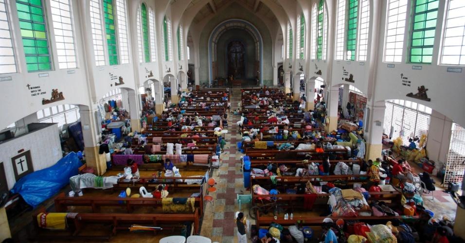 21.nov.2013 - Sobreviventes do tufão Haiyan, que devastou as Filipinas há duas semanas e pode ter matado até 4.000 pessoas, segundo estimativas oficiais, se abrigam dentro de igreja na cidade de Tacloban (a mais afetada pelo tufão)