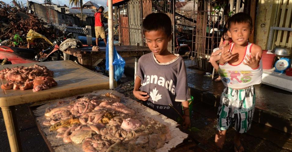 21.nov.2013  -Dois meninos intestino de suínos que estão à venda em Tacloban, Filipinas. O comércio de alimentos no país começa a reabrir em alguns locais do país