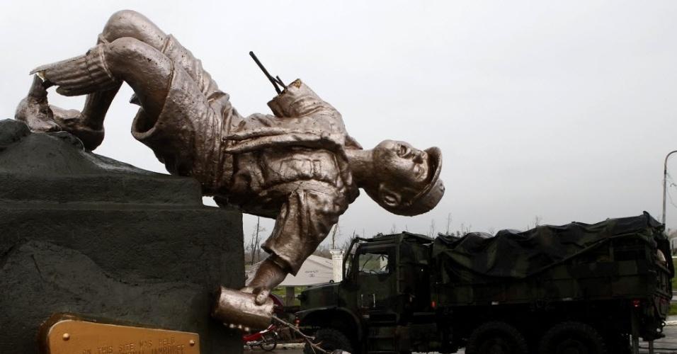 22.nov.2013 - Caminhão com suprimentos para vítimas do tufão Haiyan passa por estátua de escoteiro que foi danificada pelo tufão em Palo, na região central das Filipinas