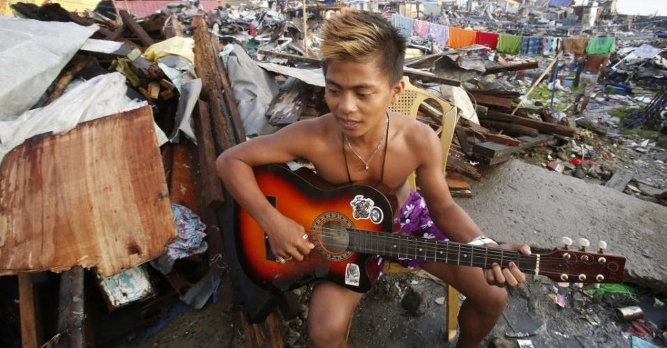 22.nov.2013 - Sobrevivente do tufão Haiyan toca violão em meio a destroços na cidade de Tacloban, nas Filipinas