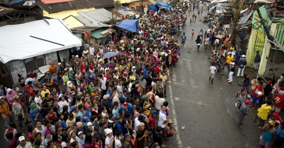 23.nov.2013 - Filipinos fazem fila durante chuva à espera de pacotes com alimentos distribuídos em Tacloban.  As Nações Unidas (ONU) elevaram nesta sexta-feira (22) seu pedido de ajuda para os afetados pelo tufão Haiyan nas Filipinas para US$ 348 milhões em uma nova chamada à comunidade internacional de doadores para atender as necessidades do país