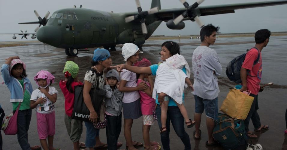 23.nov.2013 - Vítimas do tufão Haiyan aguardam no aeroporto de Tacloban, nas Filipinas, para embarcar em avião militar em direção a Manila