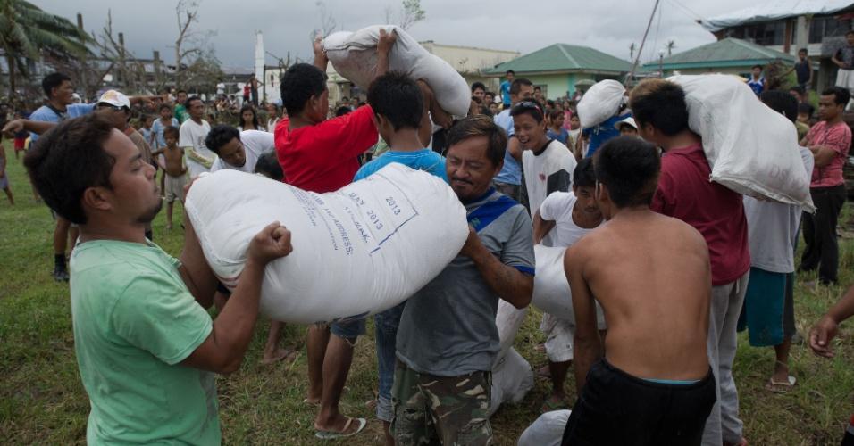 23.nov.2013 - Vítimas do tufão Haiyan carregam sacos com mantimentos jogados por helicóptero da Força Aérea filipina em La Paz, na costa leste do país