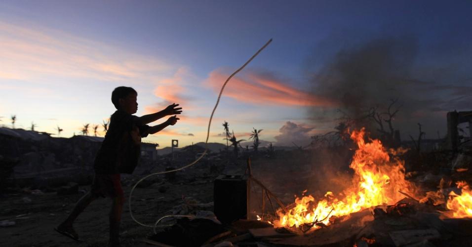 24.nov.2013 - Criança queima restos de fios de cobre para ganhar dinheiro em meio a escassez intensificada por tufão que devastou a cidade de Tacloban, nas Filipinas