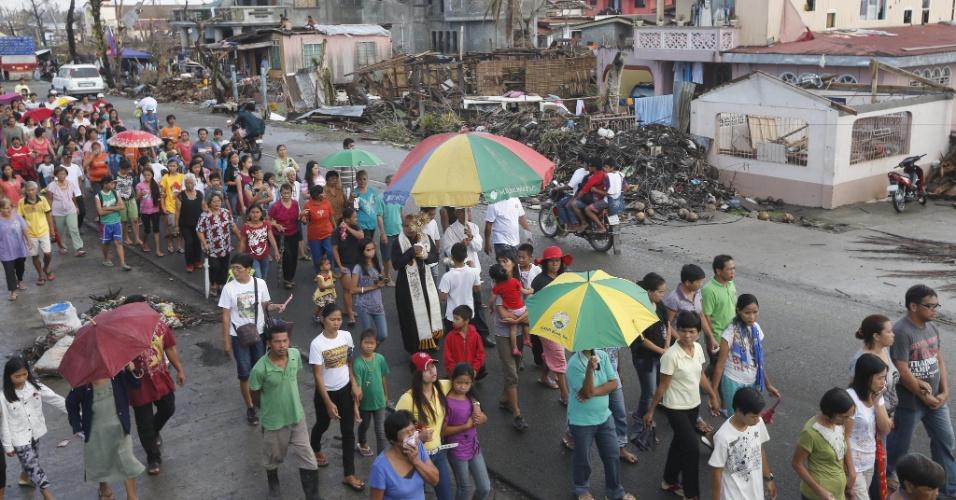 24.nov.2013 - Filipinos acompanham neste domingo (24) padre católico em  procissão simbólica por áreas danificadas pelo tufão Haiyan, em Palo. O número de mortos subiu para 5.235 e o de desaparecidos, para 1.613, disse o governo neste domingo