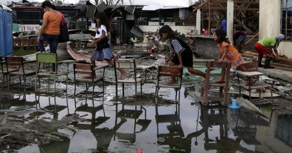 26.nov.2013 - Crianças passam por cima de cadeiras para chegarem a escola sem sujar os pés de lama em Tacloban, Filipinas. O governo filipino está planejando grandes mudanças na infraestrutura após o desastre causado pelo tufão Haiyan
