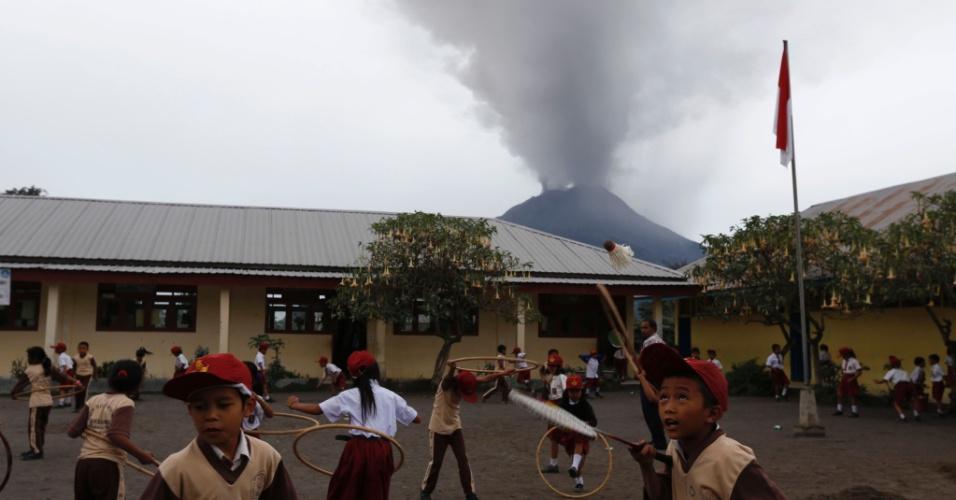 26.nov.2013 - Estudantes brincam no pátio de uma escola enquanto o vulcão Sinabun expele cinzas em Sumatra, na Indonésia