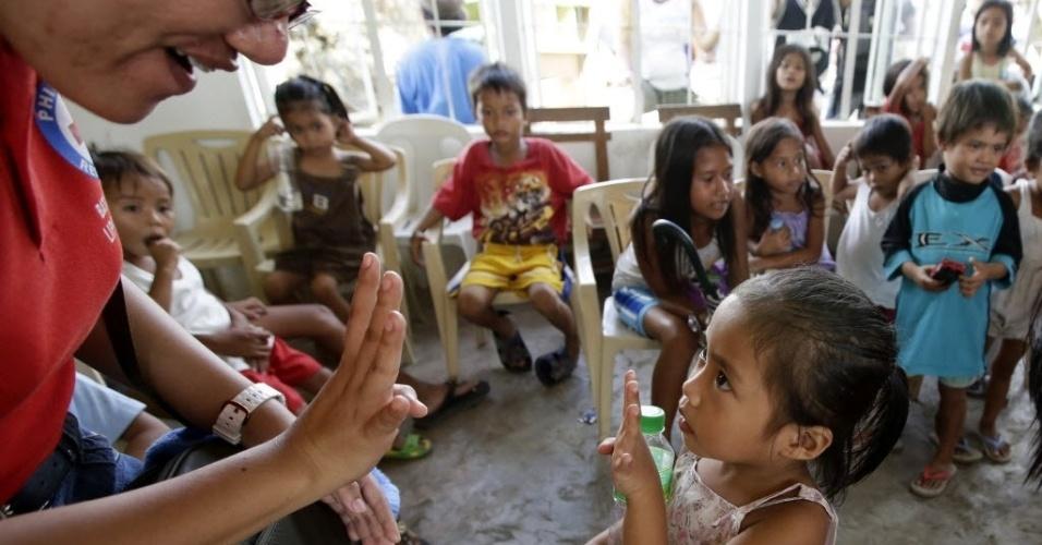 26.nov.2013 - Voluntária da Cruz Vermelha ensina menina a contar, em Tacloban, Filipinas. O governo filipino está planejando grandes mudanças na infraestrutura após o desastre causado pelo tufão Haiyan
