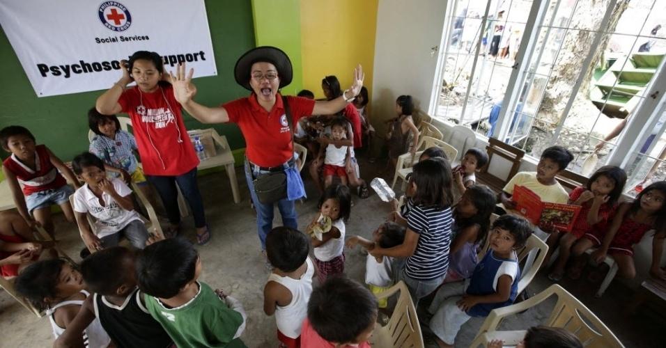 26.nov.2013 - Voluntários da Cruz Vermelha ensinam crianças em colégio na cidade de Tacloban, nas Filipinas. O governo filipino está planejando grandes mudanças na infraestrutura após o desastre causado pelo tufão Haiyan