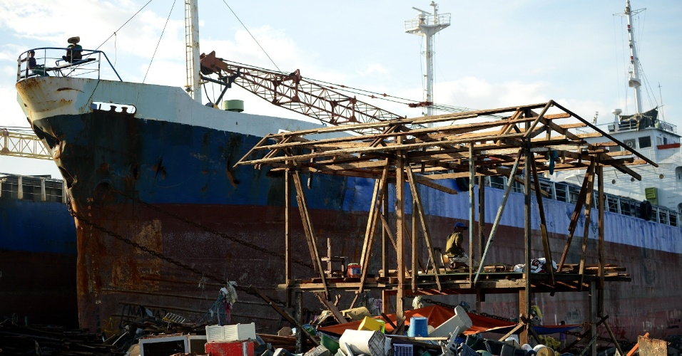 27.nov.2013 - Um homem reconstrói a sua casa próximo ao navio que que foi arrastado pelo tufão Haiyan e colidiu com casas na baía de Tacloban, na província de Leyte, na região central das Filipinas. O fenômeno climático atingiu o país no último dia 8, deixando 5.500 mortos e 3,5 milhões de deslocados. Segundo a ONG Médicos Sem Fronteiras (MSF), há locais que ainda não receberam nenhum tipo de ajuda humanitária após a passagem do tufão Haiyan