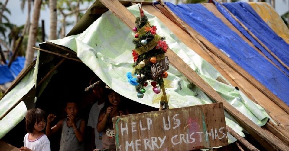 28.nov.2013 - Crianças são vistas em um abrigo improvisado onde se lê : ? Nos ajuda, Feliz Natal?, ao lado de uma árvore de Natal em Samar, Filipinas