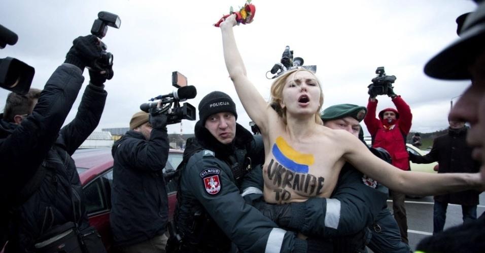 29.nov.2013 - Policial da Lituânia segura uma ativista do movimento feminista Femen durante um protesto em Vilnius, capital do país