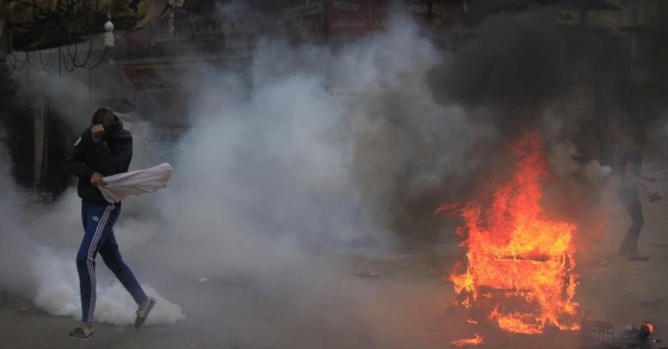 29.nov.2013 - Um apoiador da irmandade muçulmana e do presidente egípcio deposto Mohamed Mursi foge perto de pneus em chamas e de bombas de gás lacrimogêneo disparados pela polícia e Exército, durante os confrontos em El-Talbyia perto da praça Giza, ao sul do Cairo