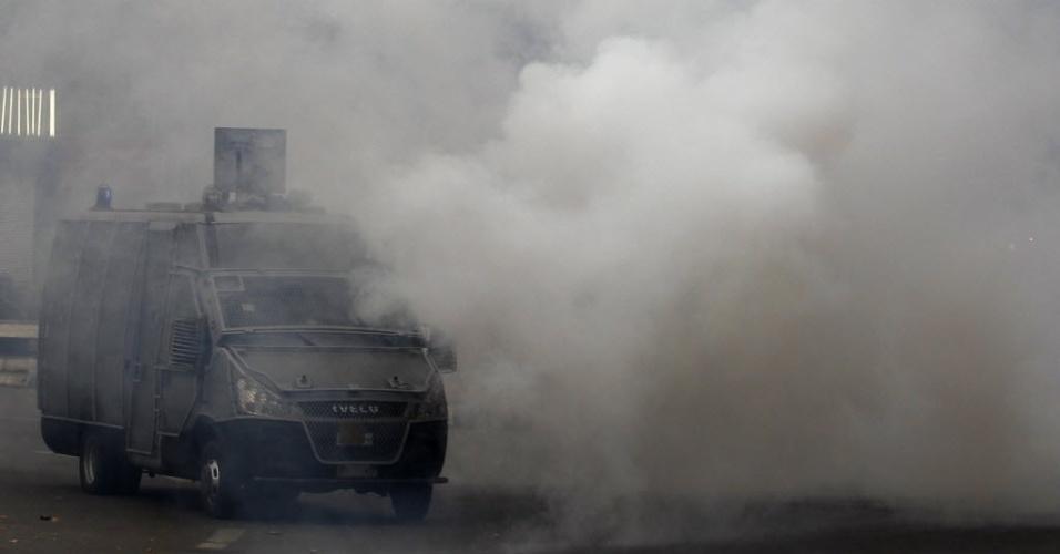 1.dez.2013 - Veículo da polícia é visto cercado por gás lacrimogêneo disparado pelas forças de segurança egípcias na praça Tahrir, no Cairo, Egito