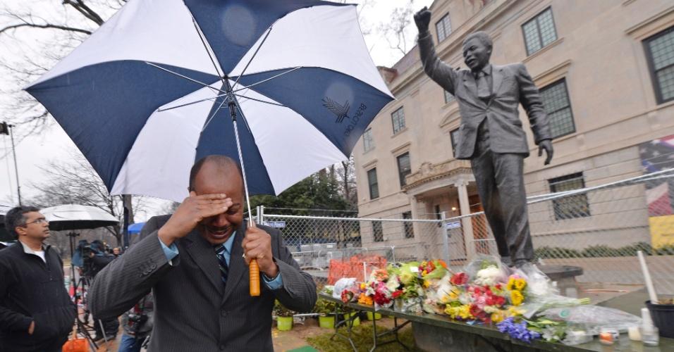 06.dez.2013 - Homem chora em frente a estátua de Nelson Mandela na embaixada da África do Sul, em Washington (Estados Unidos)