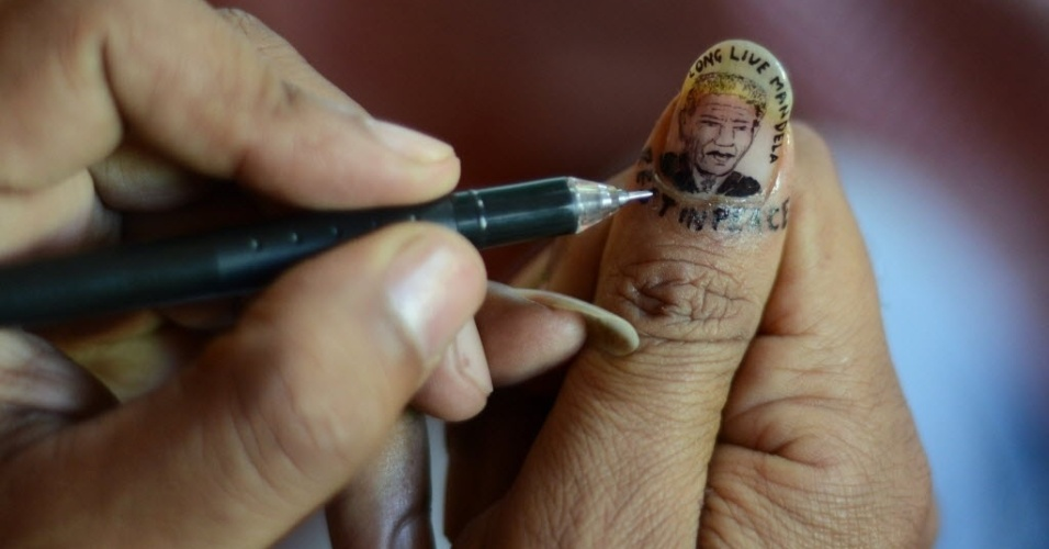6.dez.2013 - Artista indiano desenha retrato de Nelson Mandela em sua unha em homenagem ao ex-presidente da África do Sul em Siliguri, Índia, nesta sexta-feira (6)