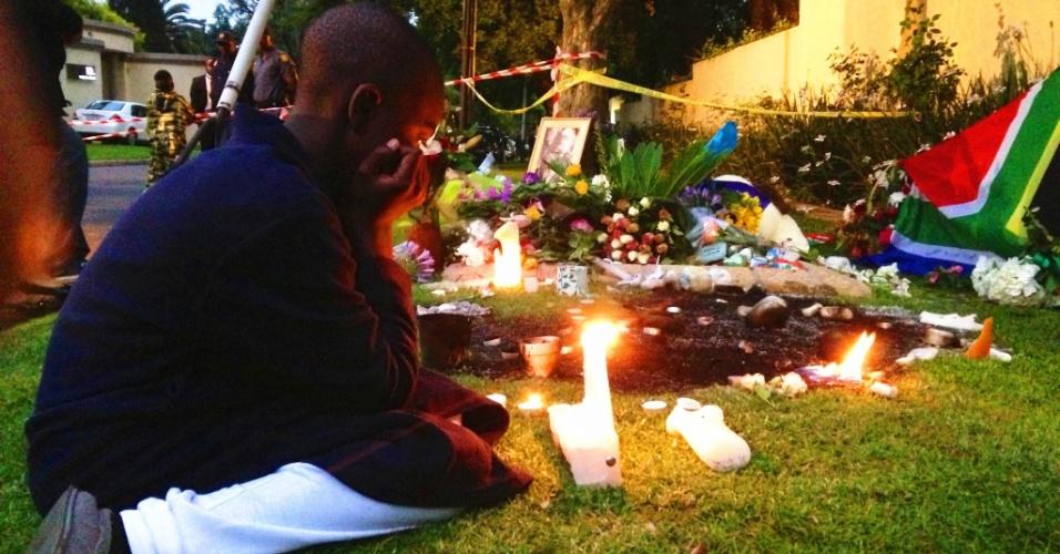6.dez.2013 - Garoto acende velas e presta homenagem a Nelson Mandela, nesta sexta-feira (6), em frente à casa do ex-presidente sul-africano, morto em Johannesburgo