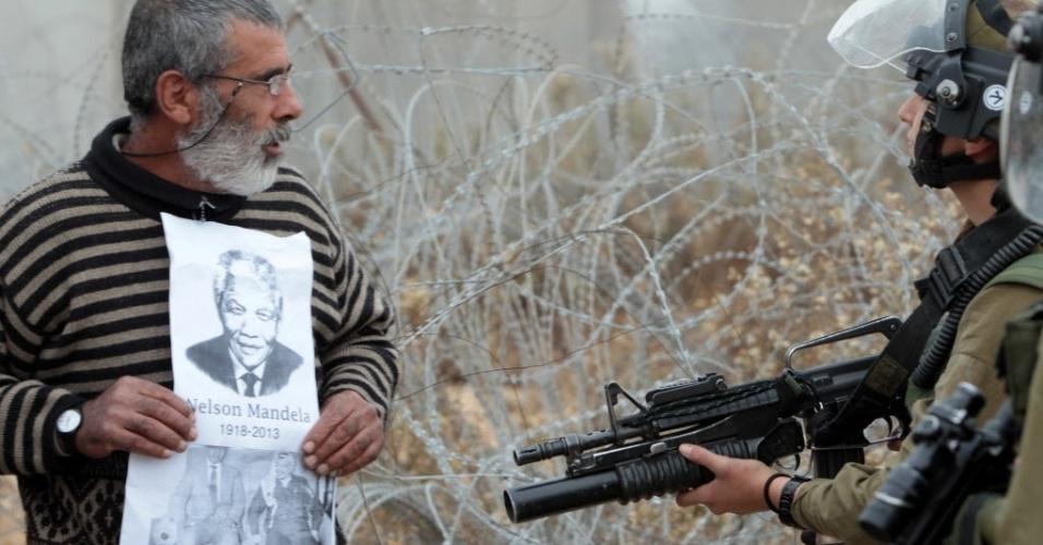 6.dez.2013 - Homem palestino segura cartaz com retrato de Nelson Mandela em frente a soldado israelense em Bilin, província palestina localizada em Ramallah, na Cisjordânia, nesta sexta-feira (6)