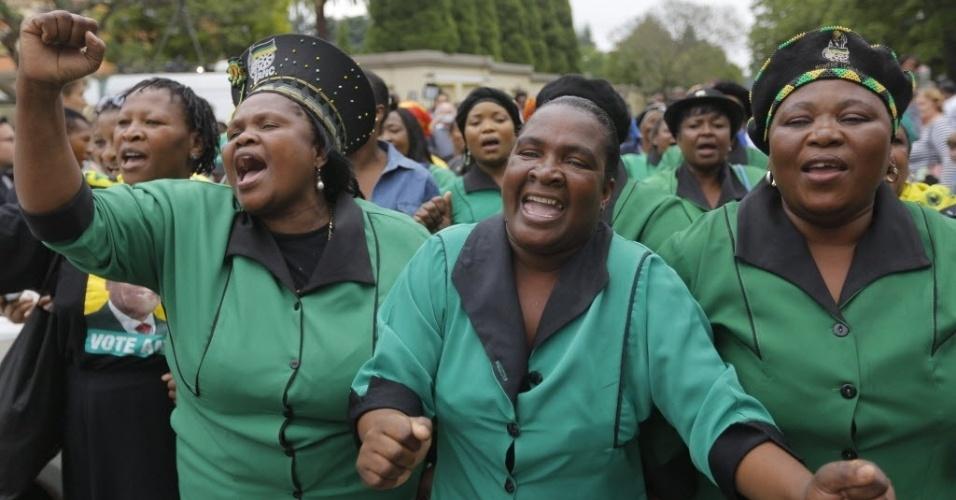 6.dez.2013 - Homens e mulheres dançam e cantam diante da casa de Nelson Mandela em Johannesburgo, nesta sexta-feira (6). Apesar do corpo do ex-presidente sul-africano ter sido transportado para Pretória, centenas se reuniam no local na manhã de hoje e muitas entoavam canções da época da luta contra o apartheid, acompanhadas por coros improvisados de sul-africanos vestidos de amarelo e verde, as cores da ANC (Congresso Nacional Africano, na sigla em inglês), o partido governista