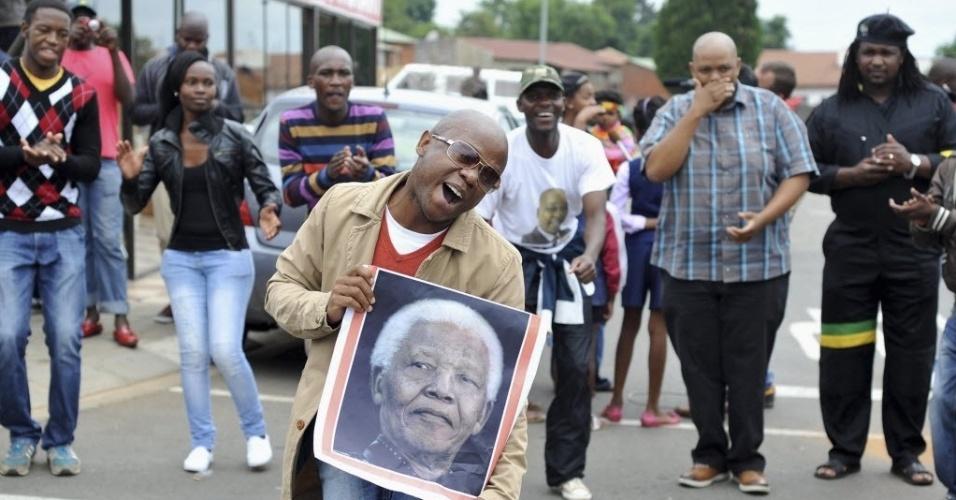 6.dez.2013 - Pessoas cantam e dançam na rua Vilakazi, em Soweto, cidade em que Nelson Mandela viveu na época da luta contra o apartheid, na África do Sul, nesta sexta-feira (6). Centenas de pessoas também dançavam e cantavam diante da casa de Nelson Mandela em Johannesburgo. Mandela morreu nesta quinta (5) aos 95 anos