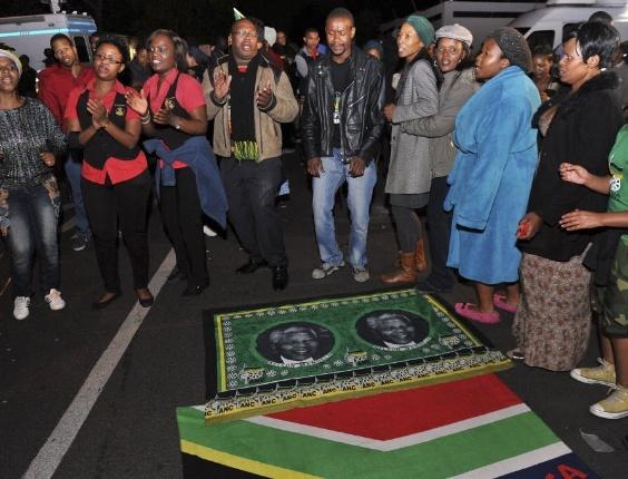 6.dez.2013 - Pessoas dançam em uma vigília noturna em frente a casa do ex-presidente da África do Sul Nelson Mandela, em Houghton, Johanesburgo, morto nesta quinta-feira (5)