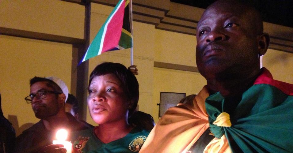 6.dez.2013 - Sul-africanos segurando velas fazem vigília em frente à casa do ex-presidente Nelson Mandela, em Johannesburgo
