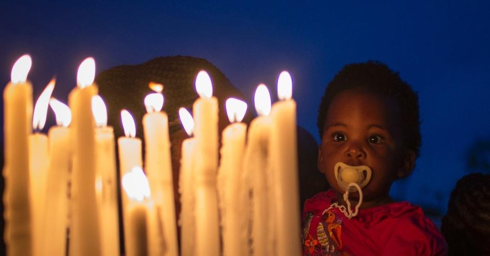 7.dez.2013 - Criança observa velas acesas do lado de fora da casa do ex-presidente da África do Sul, Nelson Mandela, neste sábado (7), em Johanesburgo. A população presta homenagens ao líder, morto na quinta-feira (5). O cortejo fúnebre a Mandela durará três dias em Pretória