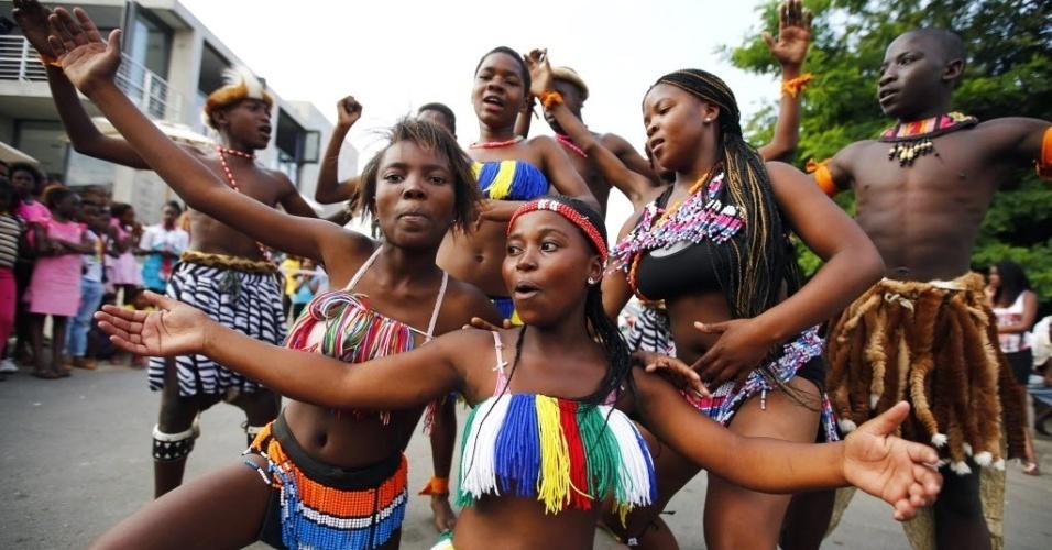 7.dez.2013 - Dançarinas se apresentam na entrada da rua Vilakazi, próxima à casa antiga de Nelson Mandela, em Soweto, onde pessoas se reúnem para homenagear o líder sul-africano, morto na quinta-feira (5)